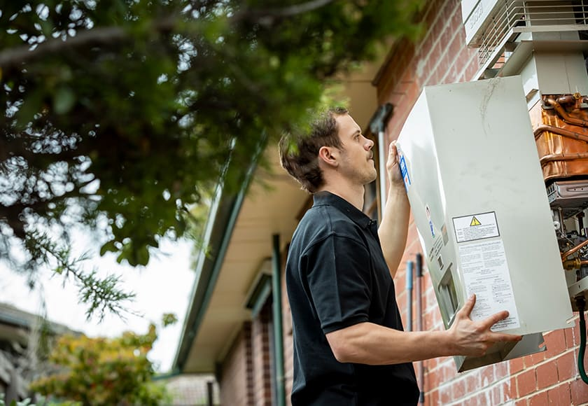gas fitter inspecting hot water system